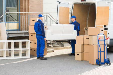 Volledige lengte van jonge mannelijke verhuizers uitvoeren bank buiten vrachtwagen op straat