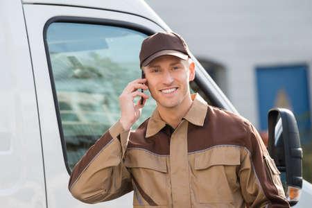 Portret van glimlachende leveringsmens die mobiele telefoon met behulp van tegen vrachtwagen