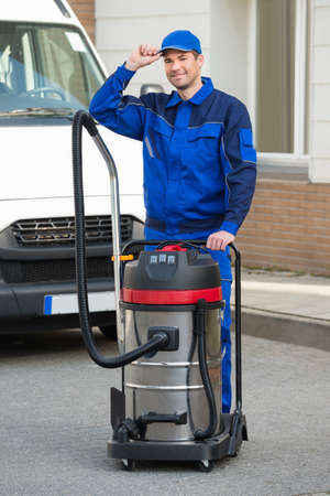Portrait of smiling male janitor with vacuum cleaner wearing cap while standing on street