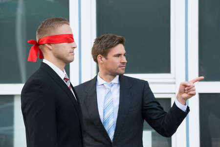 Confident young businessman assisting blindfolded partner outside office