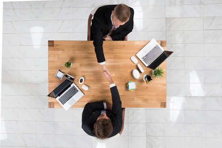 Directly above shot of businessmen shaking hands at desk in office