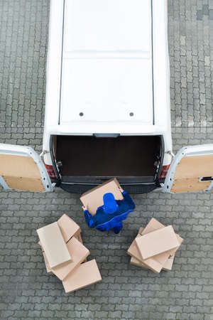 Directly above shot of delivery man unloading cardboard boxes from van on street