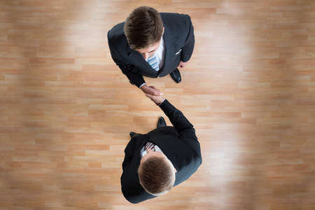 directly above: Directly above shot of businessmen shaking hands while standing on wooden floor in office Stock Photo