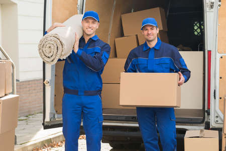 removal van: Portrait of happy delivery men carrying cardboard box and carpet outside van Stock Photo