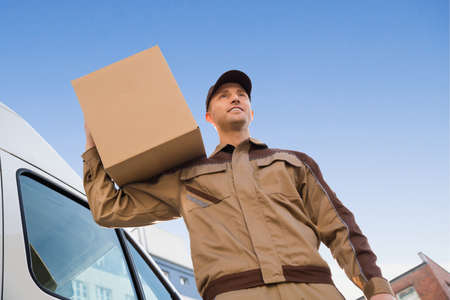 shoulder carrying: Low angle portrait of young delivery man carrying cardboard box on shoulder against sky