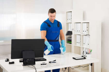 work gloves: Mid adult male worker cleaning computer desk with spray and sponge at office
