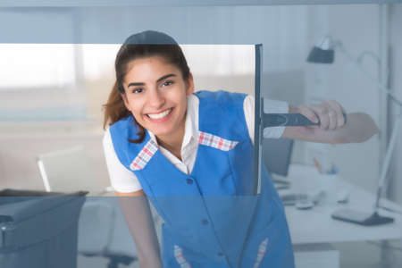 clean office: Portrait of smiling young female worker cleaning glass window with squeegee at office