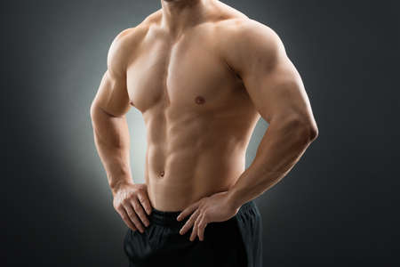 Midsection of muscular man standing with hands on hip against black background