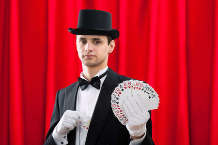 fanned: Portrait of young male magician holding fanned out cards against red curtain