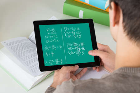 mathematical: High angle view of student learning mathematical equations on digital tablet while studying at desk