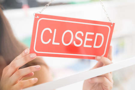store sign: Closeup of female owner holding closed sign in clothing store