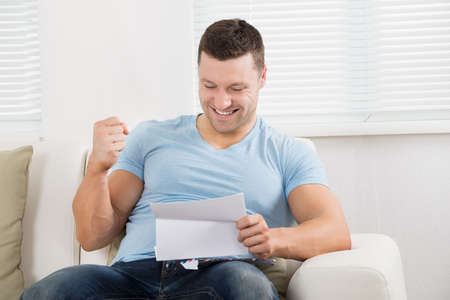 clenching: Happy mid adult man clenching fist while reading letter on sofa at home Stock Photo