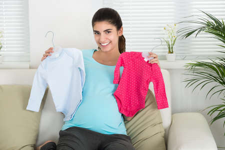 eagerness: Portrait of happy pregnant woman holding baby clothes while sitting on sofa at home Stock Photo