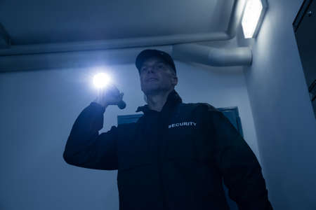 safety at work: Mature security guard searching with flashlight in office building