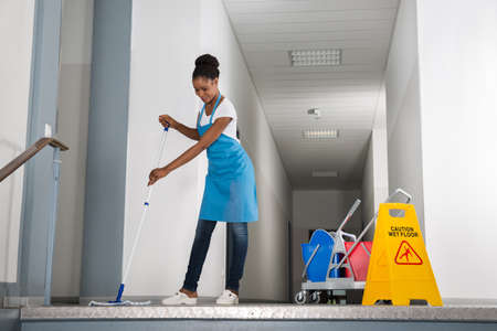 African Woman Mopping Corridor Besides Caution Sign