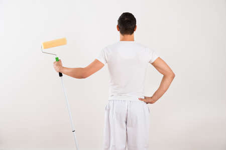 redecoration: Rear view of young man holding paint roller while standing against white wall at home