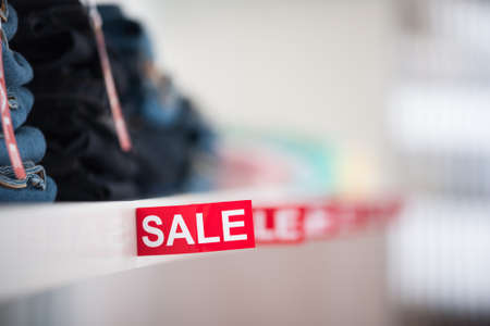 store shelf: Closeup of sale sign on shelf at clothing store Stock Photo