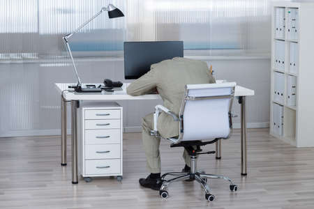 Rear view of tired businessman sleeping on desk in office