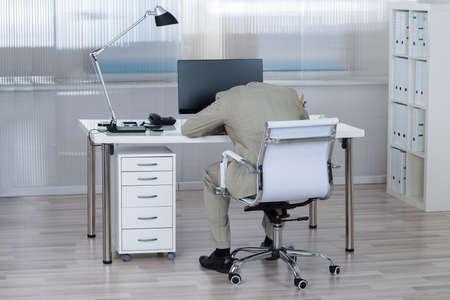 sleeping on desk: Rear view of tired businessman sleeping on desk in office