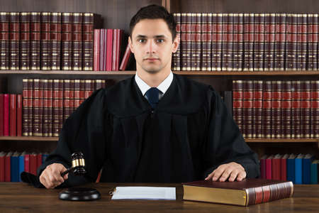 Ritratto di giudice fiducioso colpire martello alla scrivania contro libreria in aula