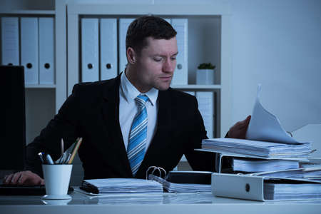 account executive: Mid adult businessman analyzing documents while working late in office