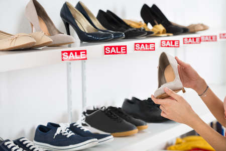 sale sign: Cropped image of young woman buying shoe in retail store