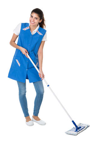 janitor: Full length portrait of happy female janitor mopping on white background