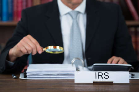 Midsection of tax auditor examining documents with magnifying glass at table in office Stockfoto