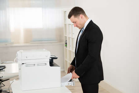 photocopier: Side view of businessman inserting paper in photocopy machine at office Stock Photo