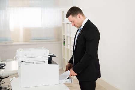fotocopiadora: Vista lateral del hombre de negocios de introducir el papel en la máquina fotocopiadora en la oficina