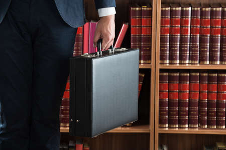 briefcase: Midsection of lawyer carrying briefcase against bookshelf in courtroom