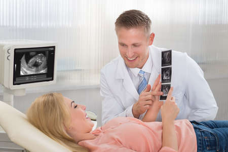 two people fertility: Young male doctor explaining ultrasound scan to pregnant woman in hospital Stock Photo