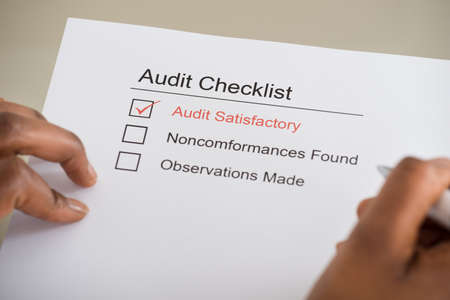 compliance: Close-up Of Persons Hand Filling Audit Checklist Form Stock Photo
