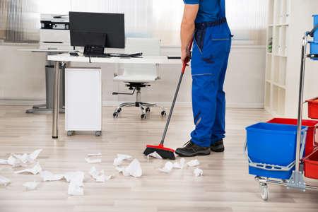 Lage deel van de mannelijke conciërge vegen papers gevallen op de vloer met een bezem in bureau Stockfoto