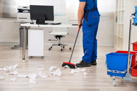Low section of male janitor sweeping papers fallen on floor with broom in office
