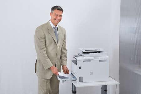 photocopier: Portrait of confident businessman using printer in office