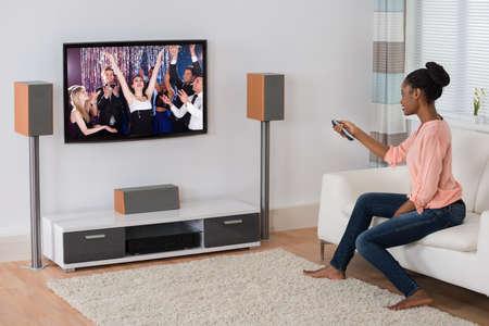 mujer viendo television: Sonrisa de la mujer africana joven sentado en el sofá viendo la película