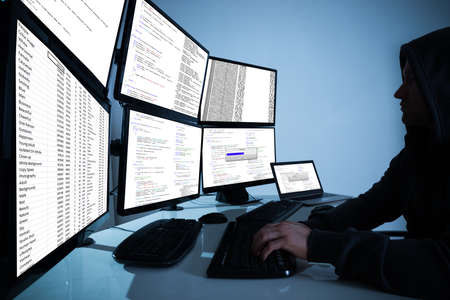 breach: Side view of hacker using computers to steal data in office Stock Photo