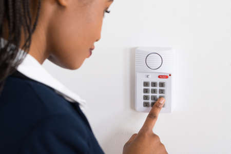 entry numbers: Close-up Of A Young African Businesswoman Pressing Button On Security System Stock Photo