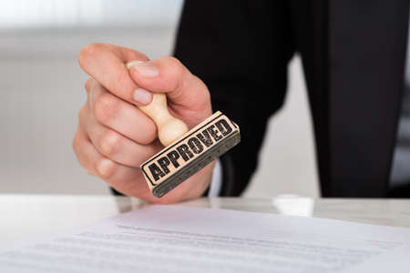 cropped image: Cropped image of businesswoman stamping approved on contract paper at desk in office