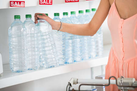 buying: Midsection of young woman buying bottle of mineral water in supermarket