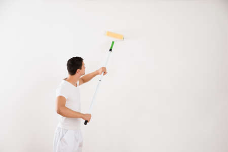 wall paint: Side view of young man using paint roller on white wall at home