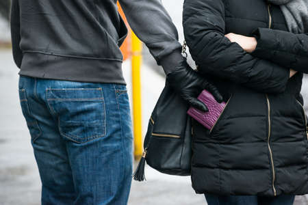 pickpocket: Midsection of young male robber stealing clutch from womans jacket on street during winter