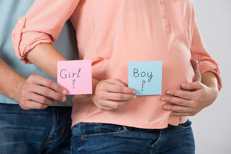 eagerness: Midsection of expecting couple holding paper with girl and boy written on it