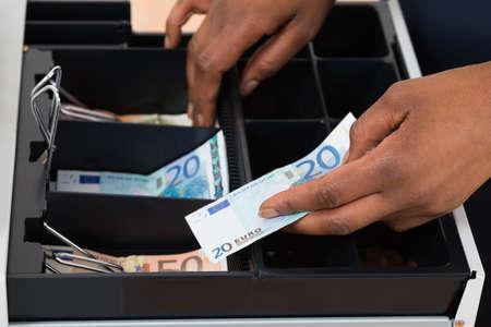 recoger: Primer plano de la mano de la persona que se considera euro Nota sobre el recipiente Foto de archivo