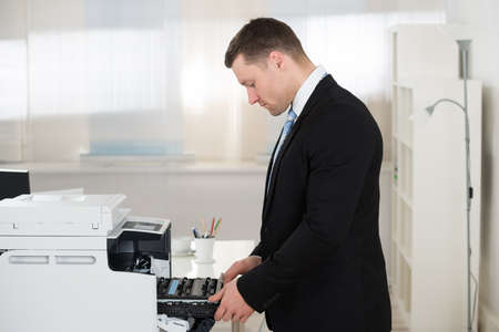 businessman in office: Side view of businessman adjusting cartridge in photocopy machine at office