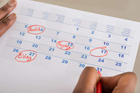 hand pen: Person Circling Important Date On Calendar With Red Marking