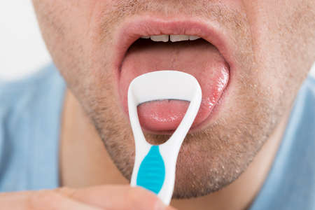 bad hygiene: Close-up of mid adult man cleaning his tongue with scraper