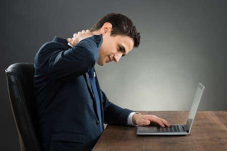 collo: Giovane uomo d'affari che soffrono di dolore al collo mentre si utilizza laptop alla scrivania su sfondo grigio