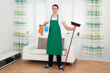 green office: Full length portrait of happy man in green apron holding cleaning equipment at home